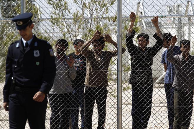 A police officer patrols a detention centre for immigrants in the Amygdaleza suburb in Athens
