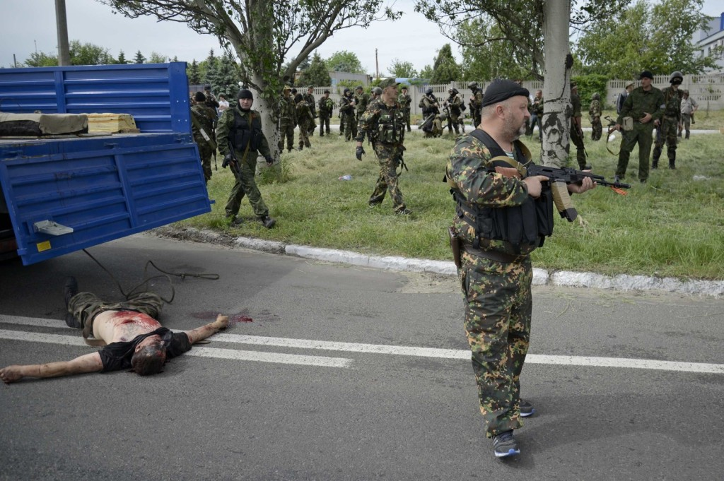 Armed pro-Russian men gather near the body a man near a checkpoint on the outskirts of Donetsk