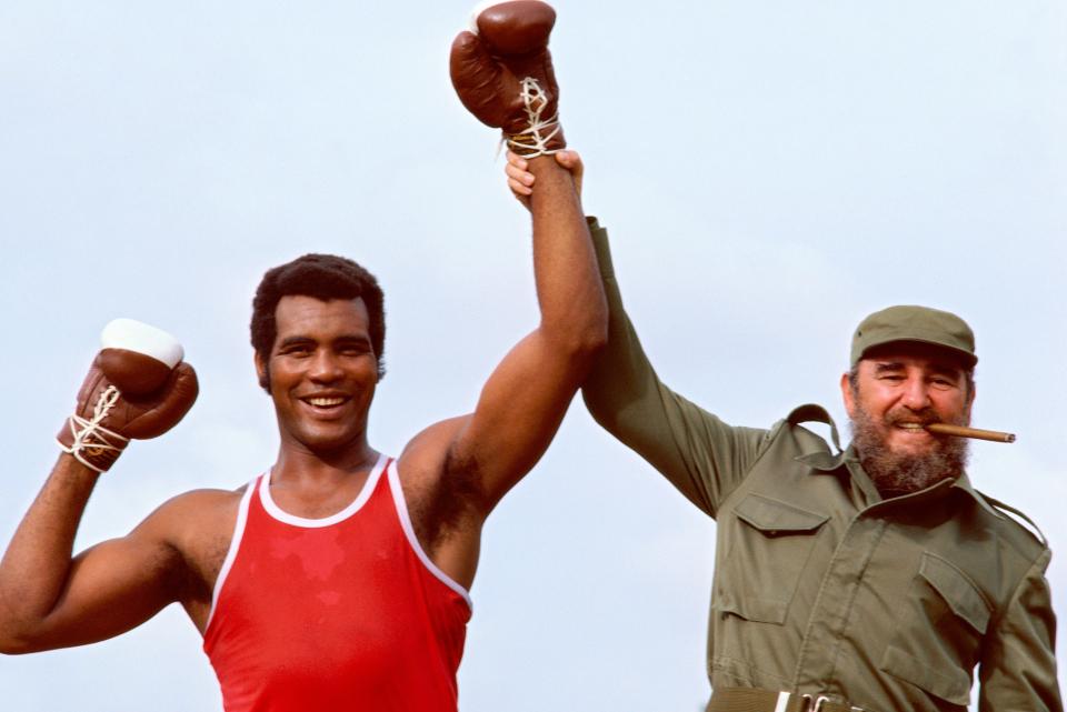 Portrait of Cuban President Fidel Castro holding the arm of heavyweight Olympic boxer Teofilo Stevenson during photo shoot. Havana, Cuba 4/1984 (Image # 1139 )