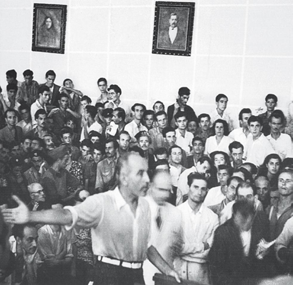 Το στρατοδικείο του ΕΛΑΣ, 13 Σεπτεμβρίου 1944. Στο εσωτερικό της Λαϊκής Σχολής. Ο όρθιος άνδρας με το πουκάμισο και το προτεταμένο χέρι είναι ο κατοχικός δήμαρχος Ηλίας Καρατζάς, κατηγορούμενος για προδοσία. (Λεύκωμα Η Καλαμάτα μέσα από το φωτογραφικό φακό του Χρήστου Αλειφέρη 1937-1974)