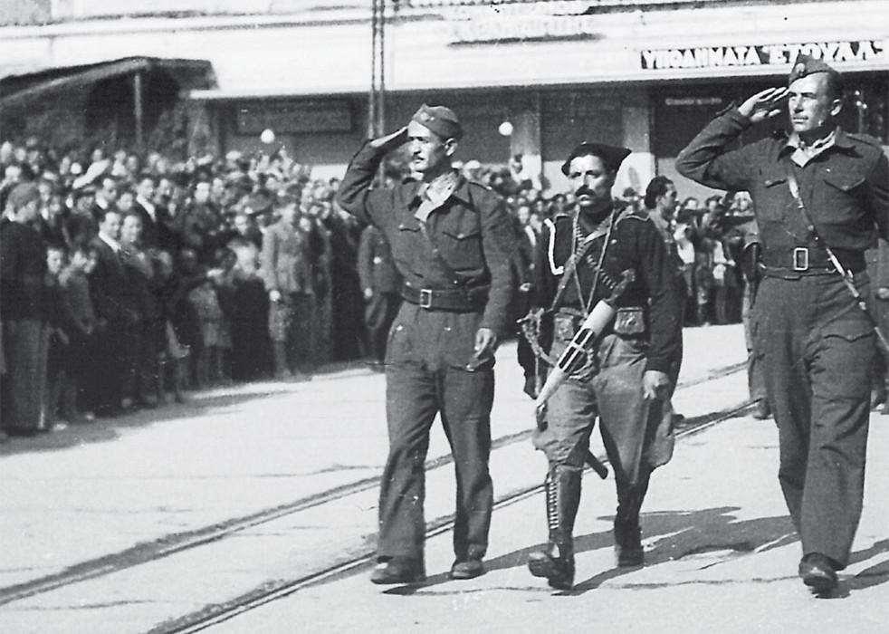 Παρέλαση στην οδό Αριστομένους, 28 Οκτωβρίου 1944. Στην παρέλαση έλαβαν μέρος τμήματα του 8ου Συντάγματος του ΕΛΑΣ, μία διμοιρία ναυτών του ελληνικού πολεμικού ναυτικού, αγγλικό τμήμα στρατού, επονίτες και επονίτισσες, τα σχολεία της πόλης και τ' αετόπουλα. Στη φωτογραφία εν μέσω δύο ανταρτών παρελαύνει ο διοικητής του ΙΙ Τάγματος του 8ουΣυντάγματος, λοχαγός Γεώργιος Αρετάκης, γνωστός με το ψευδώνυμο «Σφακιανός» λόγω της κρητικής του καταγωγής