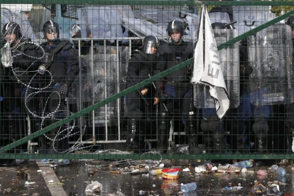 Hungarian riot police watches from behind a fence migrants protesting on the Serbian side of the border, near Roszke