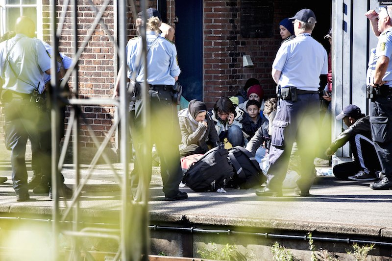 Policemen stand around refugees being contained at Padborg Station, Denmark