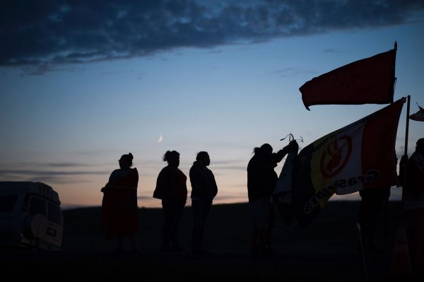 People stand with flags against the backdrop a crescent moon after sunset at an encampment where hundreds of people have gathered to join the Standing Rock Sioux Tribe's protest against the construction of the Dakota Access Pipe (DAPL), near Cannon Ball, North Dakota, on September 3, 2016. The Indian reservation in North Dakota is the site of the largest gathering of Native Americans in more than 100 years. Indigenous people from across the US are living in camps on the Standing Rock reservation as they protest the construction of the new oil pipeline which they fear will destroy their water supply.  / AFP / Robyn BECK        (Photo credit should read ROBYN BECK/AFP/Getty Images)