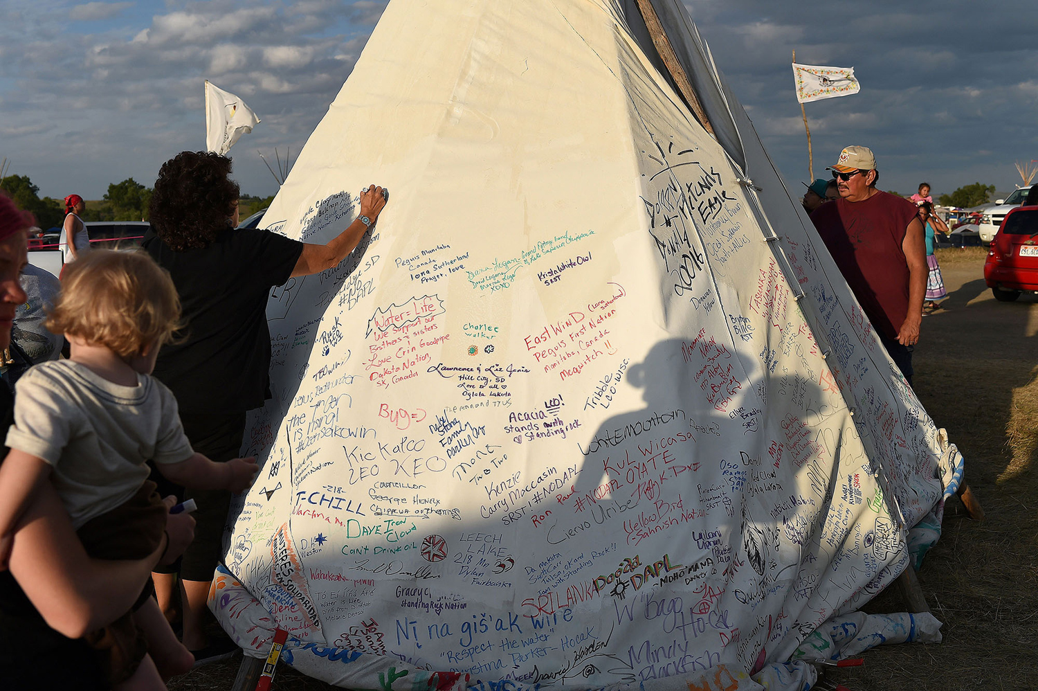 People sign a teepee with words of support for protestors at an encampment where hundreds of people have gathered to join the Standing Rock Sioux Tribe's protest against the construction of the Dakota Access Pipe (DAPL), near Cannon Ball, North Dakota, on September 3, 2016. The Indian reservation in North Dakota is the site of the largest gathering of Native Americans in more than 100 years. Indigenous people from across the US are living in camps on the Standing Rock reservation as they protest the construction of the new oil pipeline which they fear will destroy their water supply.  / AFP / Robyn BECK        (Photo credit should read ROBYN BECK/AFP/Getty Images)