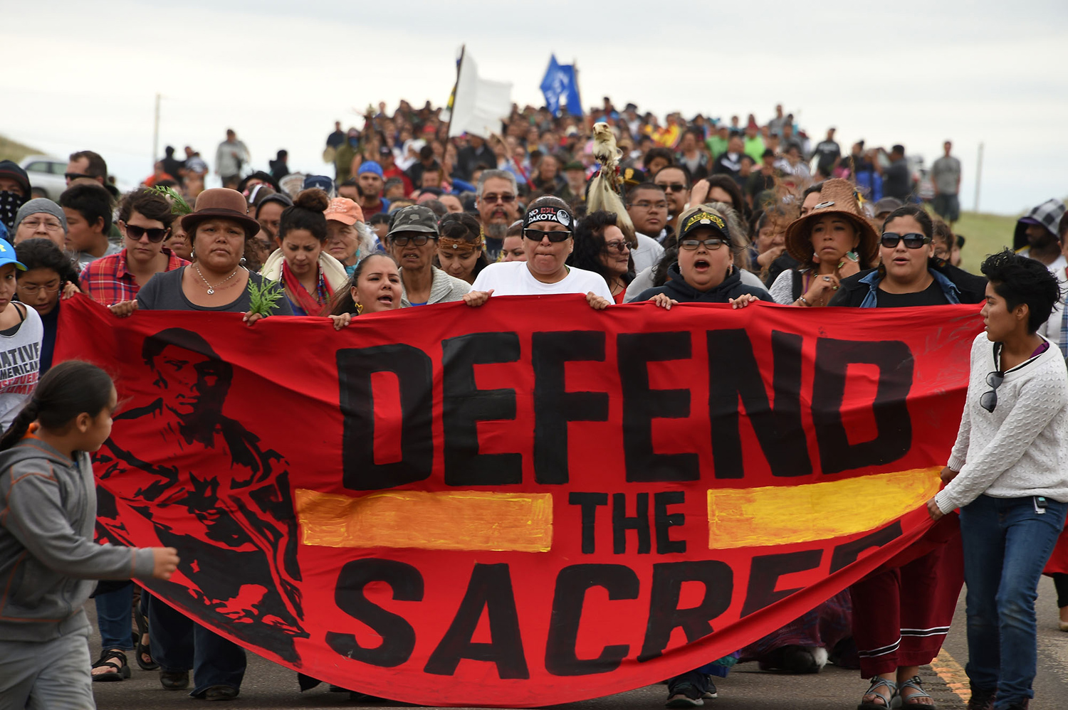 Native Americans march to a burial ground sacred site that was disturbed by bulldozers building the Dakota Access Pipeline (DAPL), near the encampment where hundreds of people have gathered to join the Standing Rock Sioux Tribe's protest of the oil pipeline that is slated to cross the Missouri River nearby, September 4, 2016 near Cannon Ball, North Dakota. Protestors were attacked by dogs and sprayed with an eye and respiratory irritant yesterday when they arrived at the site to protest after learning of the bulldozing work. / AFP / Robyn BECK        (Photo credit should read ROBYN BECK/AFP/Getty Images)