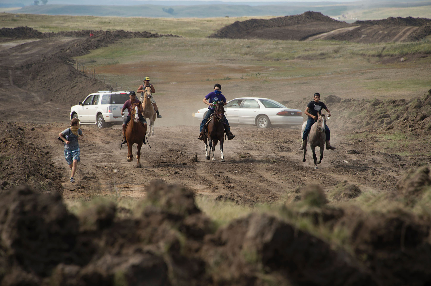 Protestors on horseback gallop away after members of the Standing Rock Sioux tribe and their supporters confronted a bulldozer crew and the private security team protecting the work site for the Dakota Access Pipeline (DAPL), near the Standing Rock Indian Reservation near Cannon Ball, North Dakota, September 3, 2016.    The protestors, who call themselves water protectors, left the area after forcing the pipeline workers and security crew to retreat.  / AFP / Robyn BECK        (Photo credit should read ROBYN BECK/AFP/Getty Images)