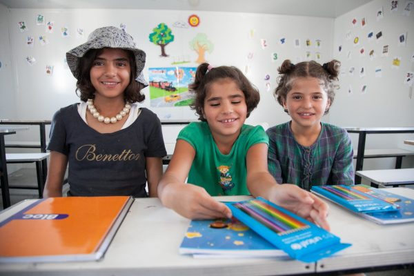 On 18 August 2016 in Athens, Greece, children attend school for 40 minutes each day in the Skaramagas refugee camp.  Isra Alsabsabi (not pictured), 19, a refugee from Aleppo, Syria teaches in English and Arabic.  Her younger sisters, Sarah (left), 12, Sham (center), 8, Salaam (right), 8, also attend the school where Esraa teaches.  The family escaped Aleppo in 2013 and spent nearly three years in Altinozu, Antakya, in Turkey not far from the Syrian border.  Their father is already living in Germany, while the rest of the family are stranded in Greece.   Several refugee teachers are teaching some 650 refugee children at the UNICEF-supported Greek NGO, Pireaus Open School, that is providing classroom supplies, teachers and technical assistance for formal education in the camp.  From 9:00am until 6:00pm classes lasting 40 minutes each are intended to reach the greatest number of children.  Next month, UNICEF will bring in 11 more classroom containers with additional supplies.     With the sudden increase of arrivals, hundreds more refugee and migrant children are becoming stranded in Greece with critical needs such as education and protection, says UNICEF. More people arrived in the first three weeks of August than all of July 2016 (1,920 for July; 2,289 as of 24 August). This new influx comes at a time when Greece is struggling to cope with a strained welfare system due to the ongoing economic crisis, leaving refugee and migrant children facing a double crisis. In total, children make up nearly 40 per cent of the current stranded population.  Getting children into education is a key priority for UNICEF and its partners in Greece, especially in the light of recent reports of children at risk. UNICEF has been supporting learning and recreational activities for refugee children in Skaramangas camp, near Athens, with the Greek NGO Piraeus Open School for Immigrants, as well as providing 11 container classrooms. UNICEF education programmes are being scaled up beyond Attica