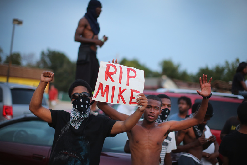 FERGUSON, MO - AUGUST 14: Demonstrators gather along West Florissant Avenue to protest the shooting death of Michael Brown on August 14, 2014 in Ferguson, Missouri. Violent protests have erupted along West Florissant in Ferguson each of the last four nights as demonstrators express outrage over the shooting death of Michael Brown by a Ferguson police officer on August 9. (Photo by Scott Olson/Getty Images) ORG XMIT: 506641261