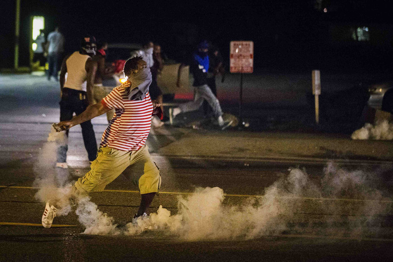 A protester picks up a gas canister to throw back towards the police after tear gas was fired at demonstrators who are continuing to react to the shooting of Michael Brown in Ferguson, Missouri August 17, 2014. Shots were fired and police shouted through bullhorns for protesters to disperse, witnesses said, as chaos erupted Sunday night in Ferguson, Missouri, which has been racked by protests since the unarmed black teenager was shot by police last week. REUTERS/Lucas Jackson (UNITED STATES - Tags: CIVIL UNREST CRIME LAW TPX IMAGES OF THE DAY) ORG XMIT: LJJ029