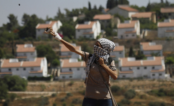 A Palestinian protester fires a stone from a slingshot towards Israeli soldiers during clashes at a weekly protest against a nearby Jewish settlement, in the West Bank village of Nabi Saleh, near Ramallah July 6, 2012. REUTERS/Mohamad Torokman (WEST BANK - Tags: POLITICS CIVIL UNREST)
