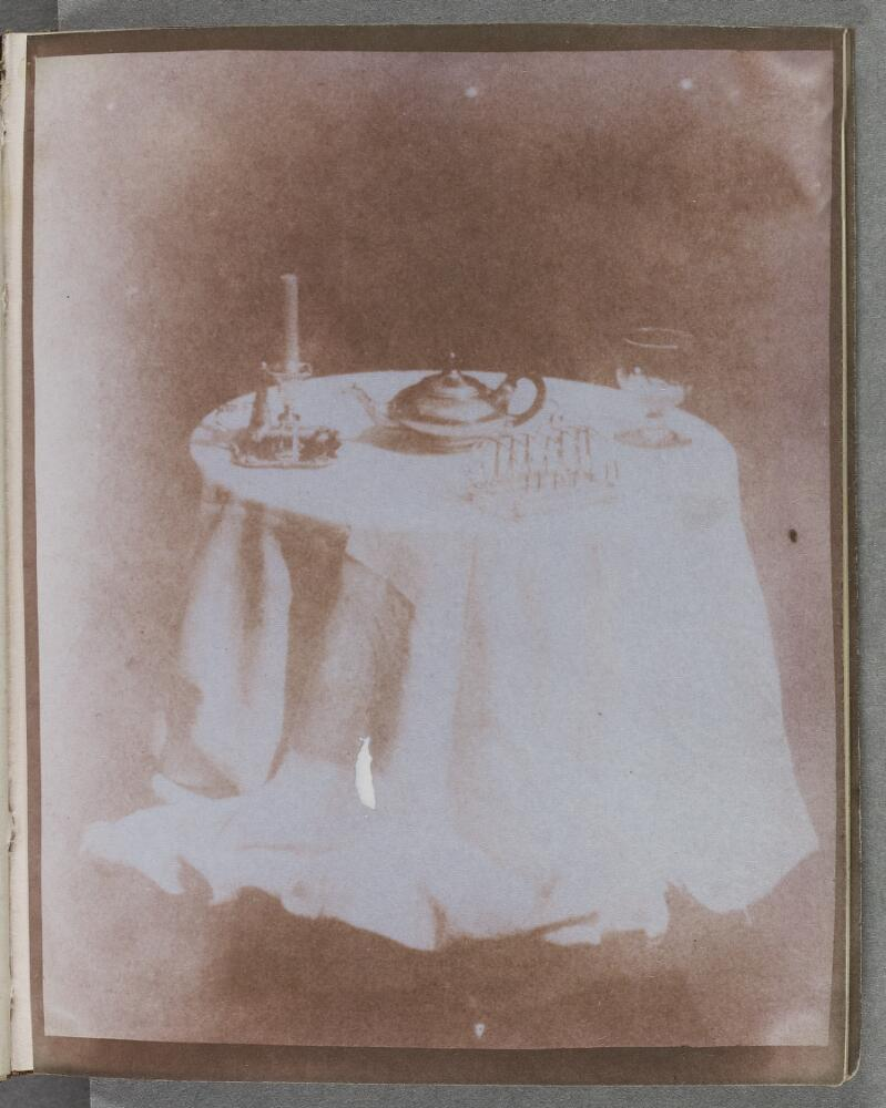 Draped tabletop with candlestick, teapot, toast rack and glass