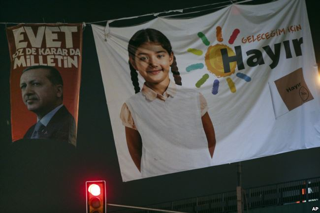 Posters of Turkey's President Recep Tayyip Erdogan, left, and the NO (Hayir in Turkish) campaign, right, for the upcoming referendum, are seen in Istanbul, Friday, March 27, 2017. Turkey is set to hold a referendum on April 16 on switching to a presidential system _ a move critics fear will concentrate too many powers in the hands of  Erdogan. (AP Photo/Emrah Gurel)