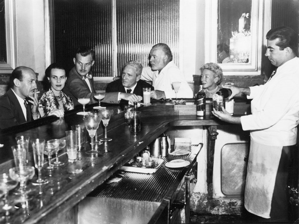 "EH 5084P not dated, ca. 1955 La Floridita, Havana, Cuba. Roberto Herrera, Byra ""Puck"" Whittlesey, John ""Bumby"" Hemingway, Spencer Tracy, Ernest Hemingway, and Mary Hemingway. Please credit: ""Ernest Hemingway Photograph Collection, John Fitzgerald Kennedy Library, Boston."""