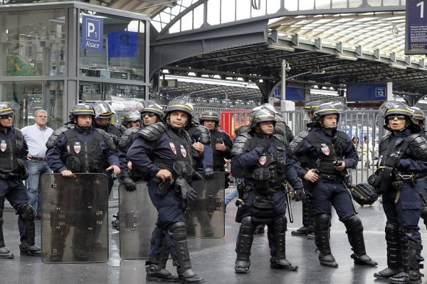 French riot police officers secure the departure of commuters as railway workers and Labor unions members attend a demonstration against the French government and labor law reforms at Gare Du Nord Station in Paris France, Wednesday June 8, 2016. Workers of France's national rail service demonstrate as part of months of protests over changes to labor protections. (AP Photo/Francois Mori)