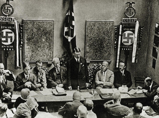 Original Caption: Founding of the Nazi Party in Munich, 1925. From left: Rosenberg, Buch, Schwarz, Hitler, Gregor Strasser, Himmler. Lower right: Julius Streicher. Photograph.